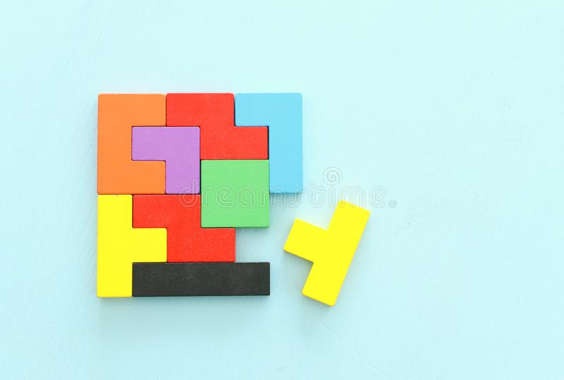 Business concept image of a colorful square tangram puzzle, over wooden table royalty free stock photo