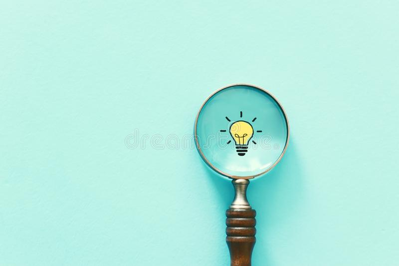 Business concept image. Magnifying glass and lamp. Finding the best idea and inspiration among others royalty free stock image