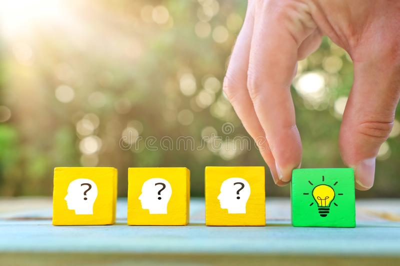 Business Concept image of revealing an idea, finding the right solution during creative process. Hand picking cube with bright. Light bulb stock image
