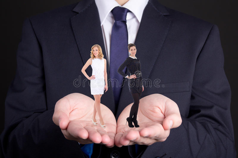 Business concept - man holding two women in his hands. Business concept - men in suit holding two women in his hands stock photos