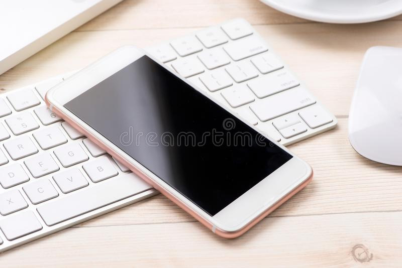 Business concept - mobile phone over laptop keyboard stock photo