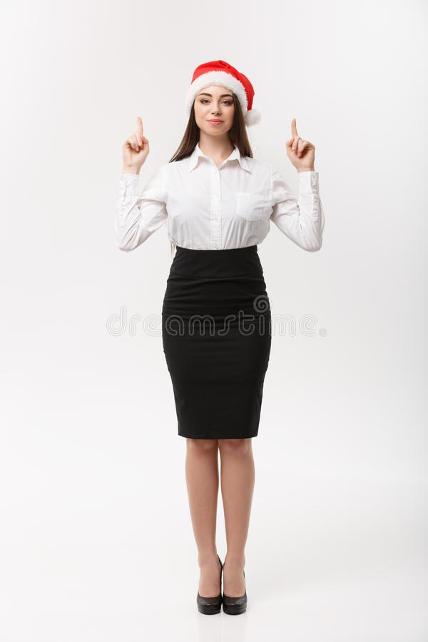 Business Concept - Modern caucasian business woman in the white studio background pointing finger upward presenting. Product stock photo