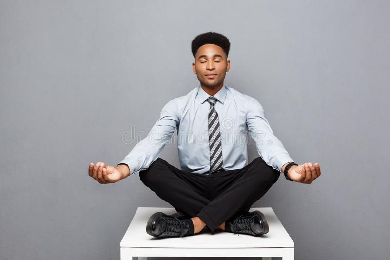 Business Concept - portrait of african american businessman doing meditation and yoga in before working. royalty free stock images
