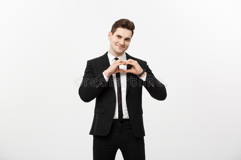 Business Concept: Portrait of charming attractive businessman holding hands in heart gesture and lifting eyebrows while stock images