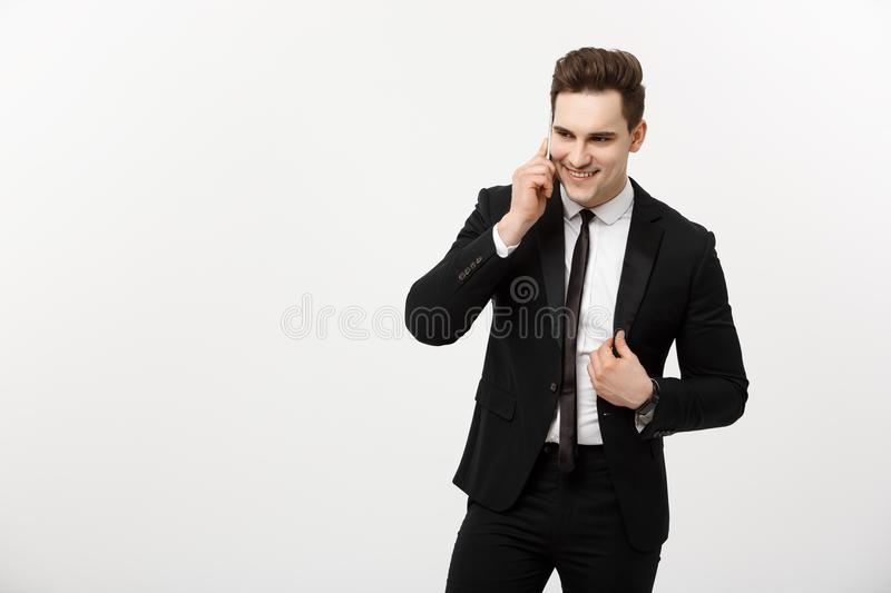 Business Concept: Portrait of a cheerful businessman in smart suit talking on the smart phone isolated on a white royalty free stock photos
