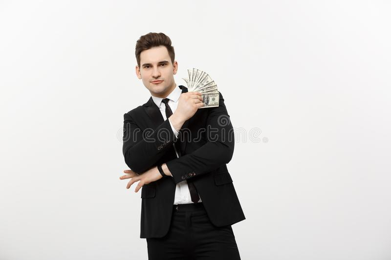 Business Concept: Portrait handsome businessman suit holding fan of dollar cash isolated over white gray background. stock photo