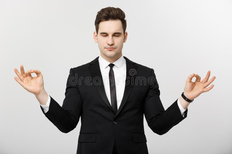 Business Concept - portrait of handsome caucasian businessman doing meditation and yoga in before working royalty free stock images