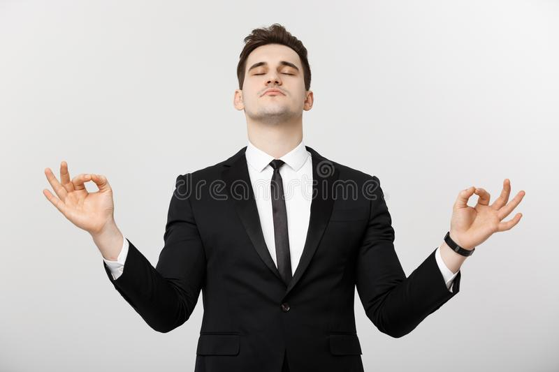 Business Concept - portrait of handsome caucasian businessman doing meditation and yoga in before working stock photo