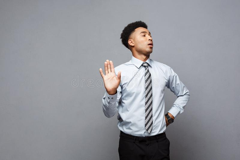 Business concept - portrait of stressed African American business man showing stop sign with hand on grey background. Business concept - portrait of stressed royalty free stock photo