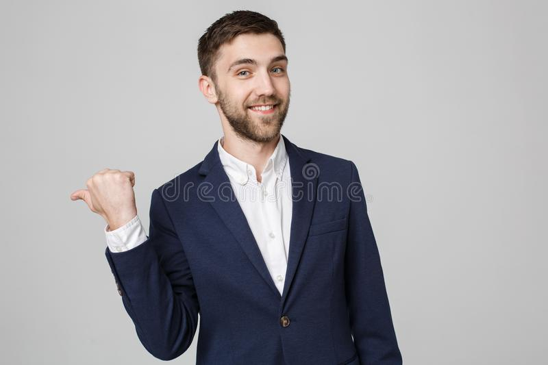 Business Concept - portrait young successful businessman pointing finger over dark background. Copy space. stock images