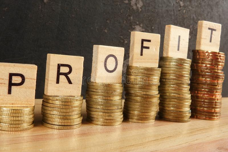 Business concept with PROFIT word on wooden plate onto hike trend stacked of coins. royalty free stock images