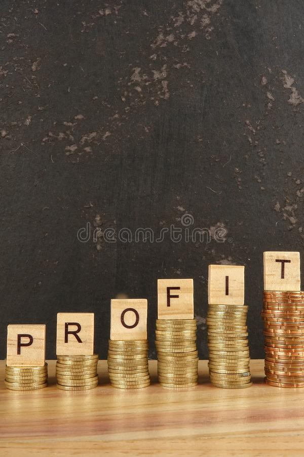 Business concept with PROFIT word on wooden plate onto hike trend stacked of coins. stock photo