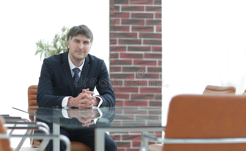 Project manager sitting at a table in an empty conference room stock photo