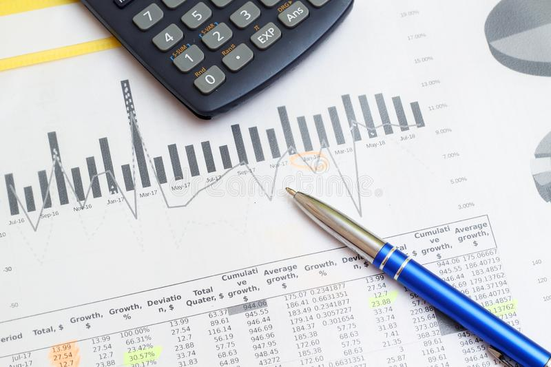 Business concept with a report and a calculator. Business report with figures and graphics, a calculator royalty free stock photography