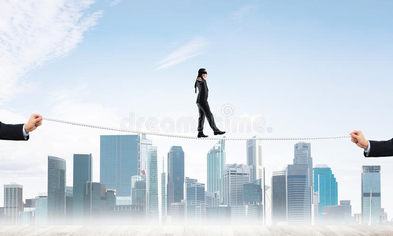 Business concept of risk support and assistance with man balancing on rope. Businessman with blindfolder on eyes walking on rope over cityscape background royalty free stock images