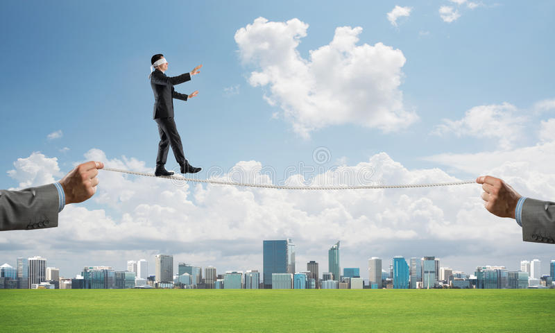 Business concept of risk support and assistance with man balancing on rope. Businessman with blindfolder on eyes walking on rope over cityscape background stock image