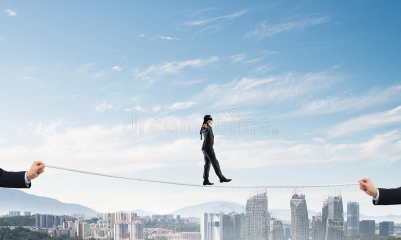 Business concept of risk support and assistance with man balancing on rope. Businessman with blindfolder on eyes walking on rope over cityscape background royalty free stock photos