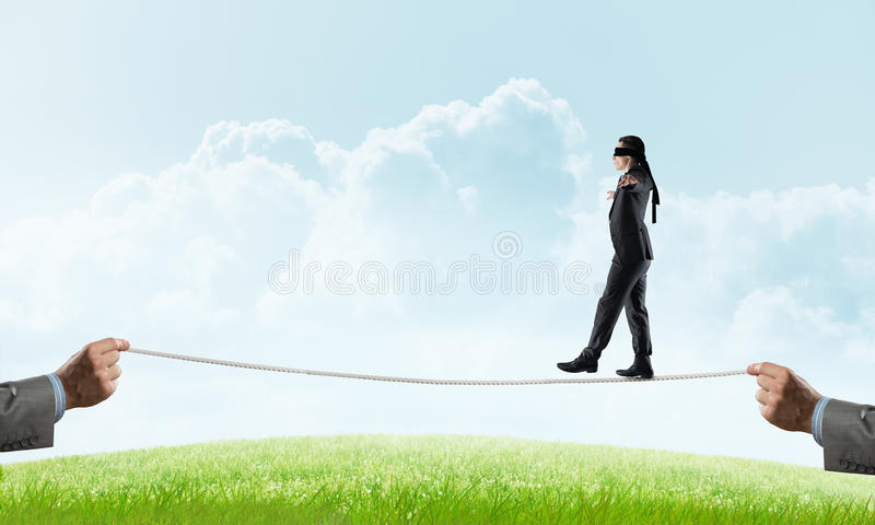 Business concept of risk support and assistance with man balancing on rope. Businessman with blindfolder on eyes walking on rope over natural background royalty free stock image