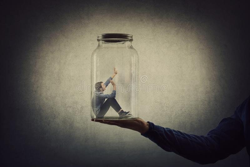 Business concept with a scared tiny man trapped inside a glass jar held by his gigantic boss hand. Surreal nightmare, helpless. Captive employee victim of abuse stock image