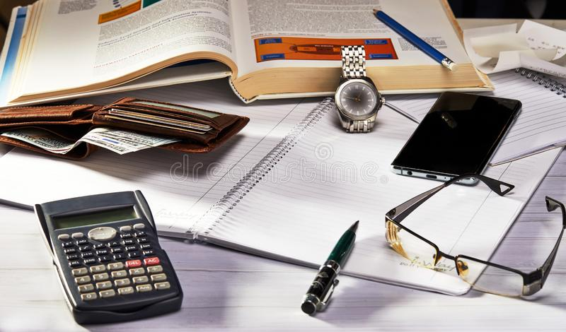 Business concept. Side view glasses, smartphone, notebook and pen, clock and calculator, purse on wooden table. Selective focus stock photo