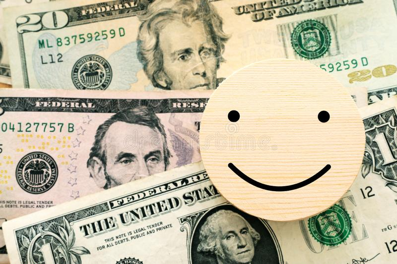 Business concept of stack of money and smiley sign. Satisfied customer, and high income or financial growth.  stock images