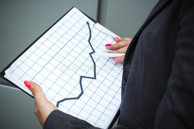 Business concept of success and growth. A successful woman boss, in a suit and wearing glasses, holds a tablet with charts stock image