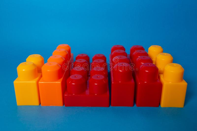 Business concept of success, teamwork and building a business. Color toy blocks on blue background royalty free stock images