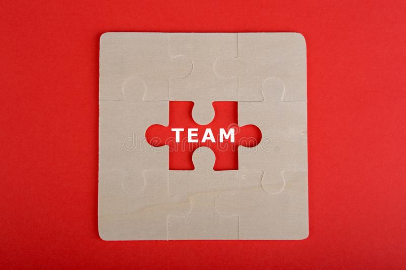 Business concept - Team word written on piece of jigsaw puzzle. On red background, teamwork, communication, choice, career, cooperation, idea, motivation royalty free stock images