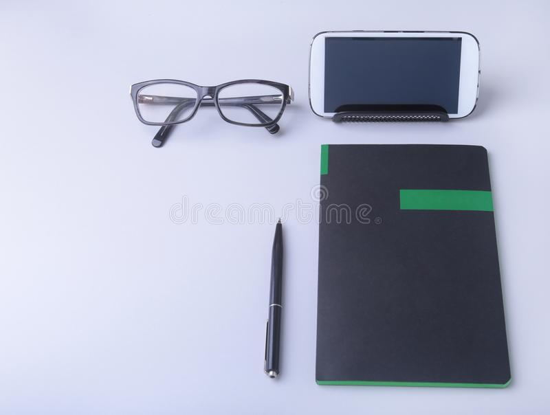 Business concept. Top view of kraft spiral notebook, glasses, smartphone and black pen isolated on background for mockup. stock images