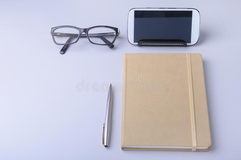 Business concept. Top view of kraft spiral notebook, glasses, smartphone and black pen isolated on background for mockup. stock photography