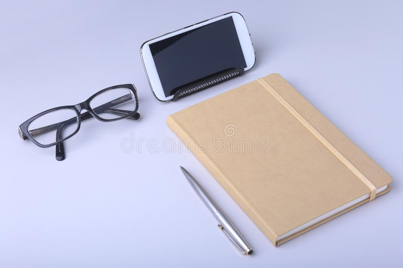 Business concept. Top view of kraft spiral notebook, glasses, smartphone and black pen isolated on background for mockup. stock photo