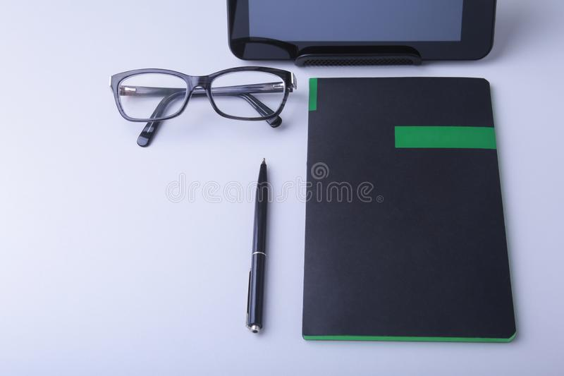 Business concept. Top view of kraft spiral notebook, glasses, smartphone and black pen isolated on background for mockup royalty free stock photo