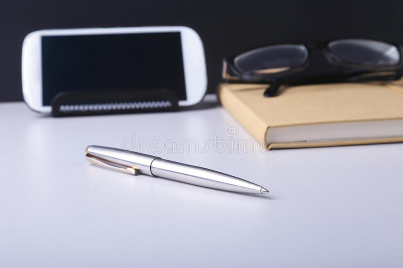 Business concept. Top view of kraft spiral notebook, glasses, smartphone and black pen on background for mockup royalty free stock images