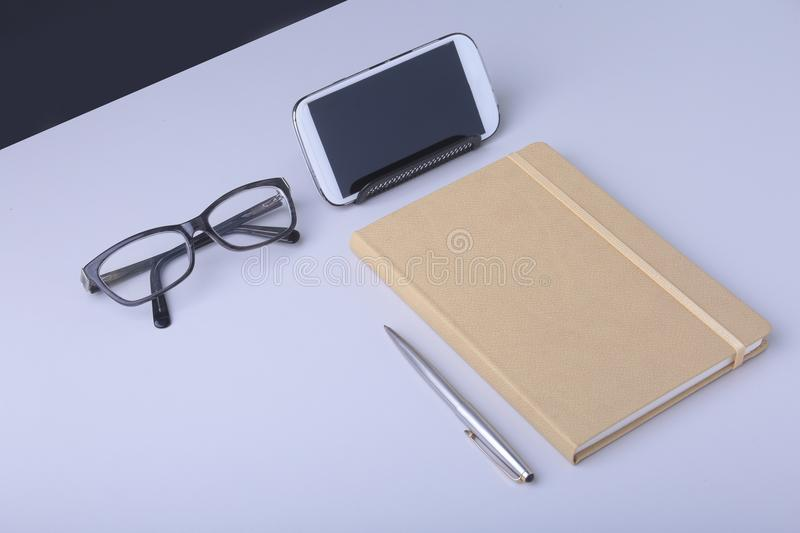 Business concept. Top view of kraft spiral notebook, glasses, smartphone and black pen isolated on background for mockup. royalty free stock photo