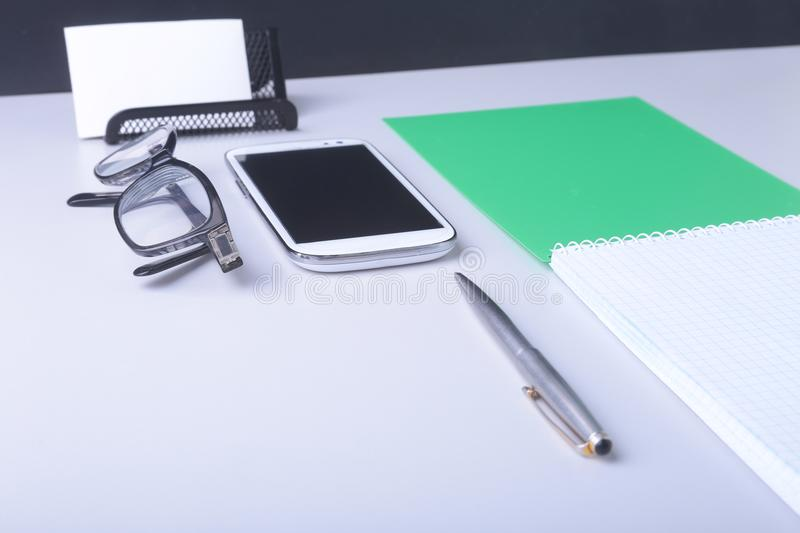 Business concept. Top view of kraft spiral notebook, glasses, smartphone and black pen isolated on background for mockup. royalty free stock images