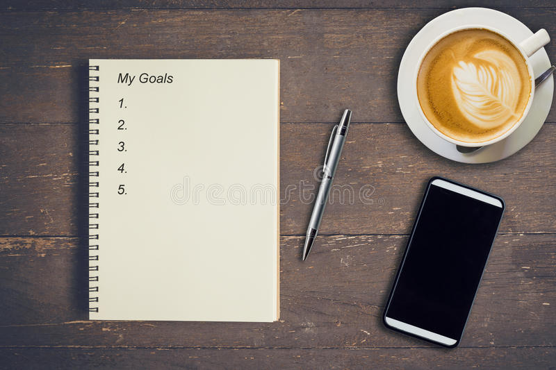 Business concept - Top view notebook writing My Goals, pen, coffee cup, and phone on wood table. royalty free stock photography