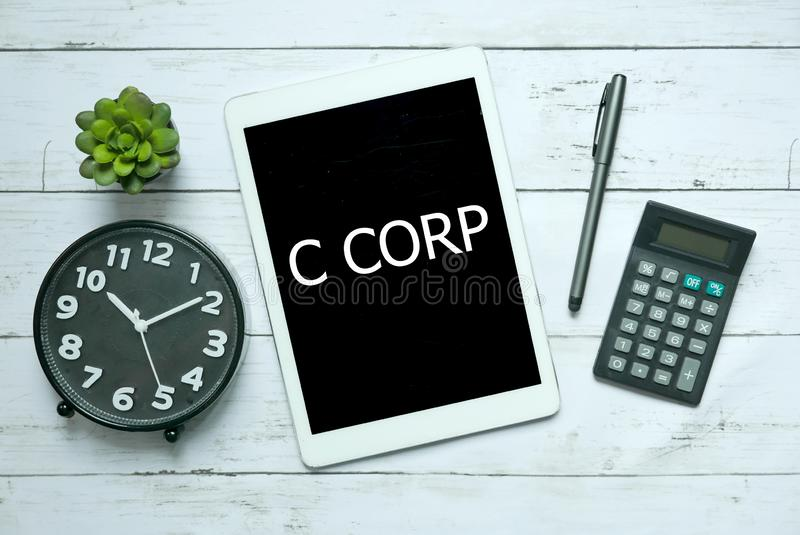 Business concept. Top view of plant,clock,calculator,pen and tablet written with C Corp on white wooden background. Business concept. Top view of plant,clock royalty free stock photo