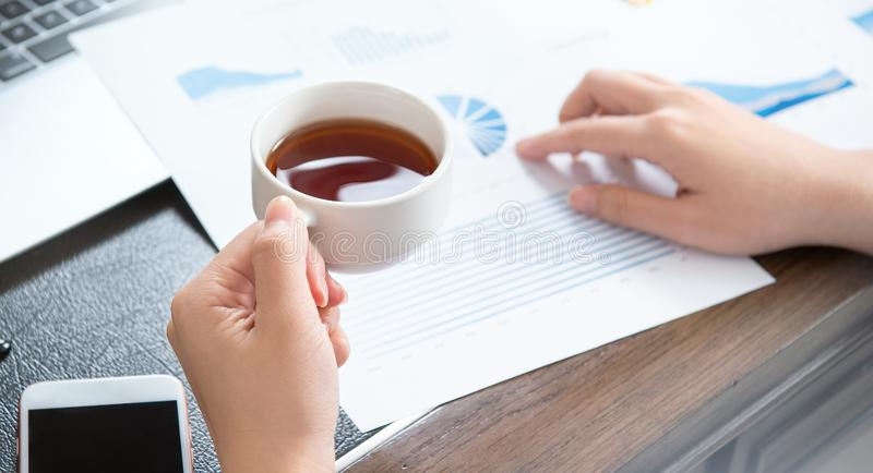 Business concept. Woman reading reports and drinking for rest in office table. Backlighting, sun glare effect, close up, side view stock images