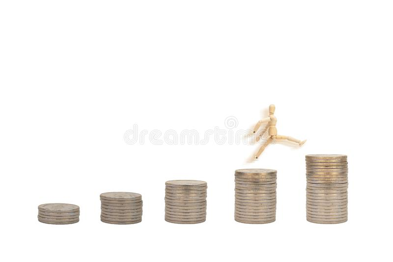 Wooden figure mannequin jumping to the top of stacked silver coins isolated on white background. Business Concept : Wooden figure mannequin jumping to the top stock images
