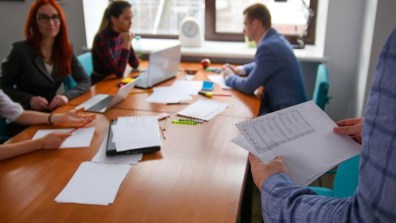 Business concept. A working team having a conference. A man brings the documents stock photo