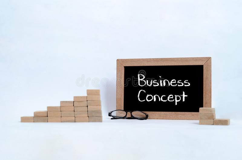 Business concept written on the blackboard. Eye glasses and Wood block stacking as step stair symbol of business concept stock images