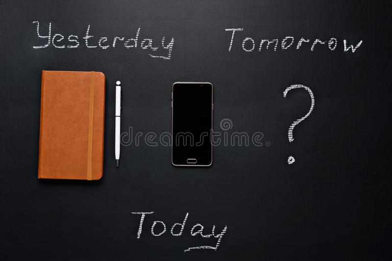 Business concept, Yesterday - a paper notebook with a pen, Today - a smartphone, What will happen tomorrow royalty free stock images