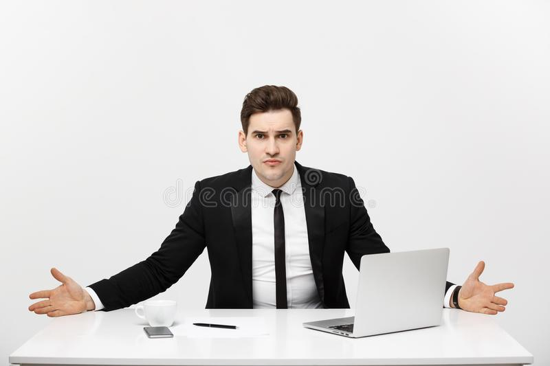Business Concept: Young businessman working in bright office, sitting at desk, using laptop with serious facial royalty free stock image