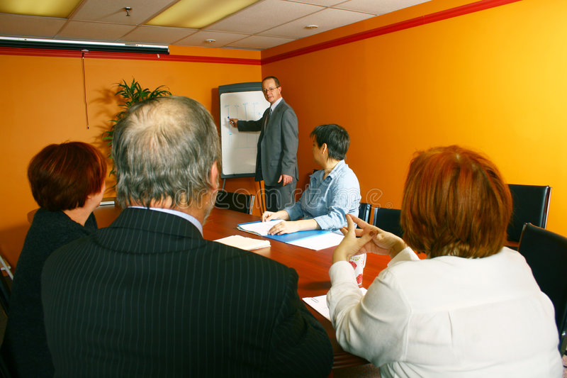 Business Conference. Four businesspeople sitting at a conference table, while a businessman stands in front of them making a presentation on a board in the royalty free stock photos