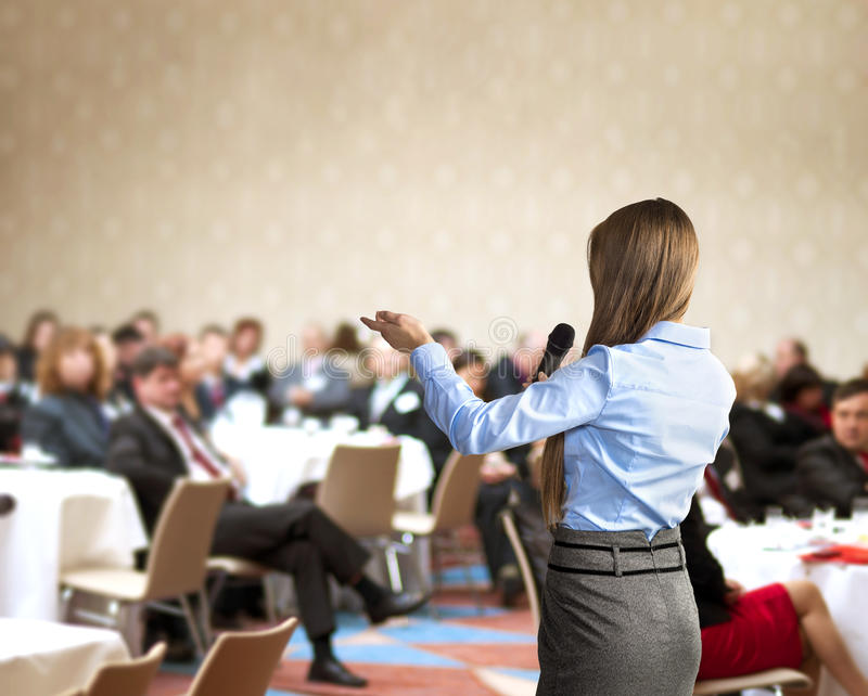 Business conference. Beautiful business woman is speaking on conference stock images