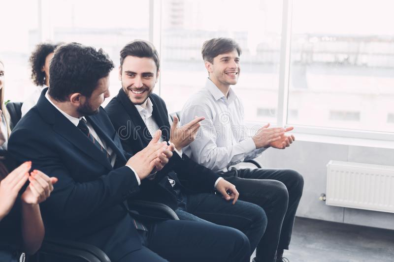 Businessmen discussing something at conference, applauding to speaker stock photo