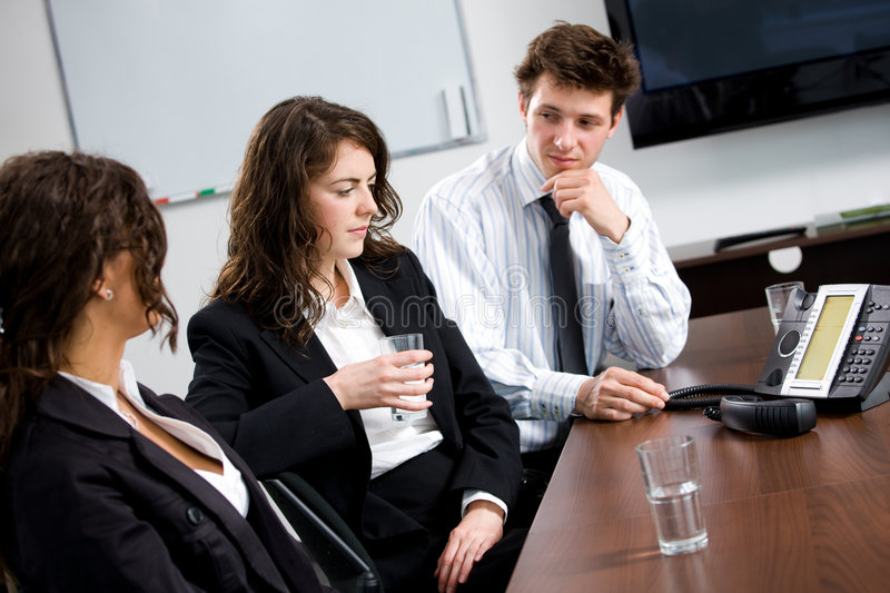 Business conference call. Businesspeople sitting on meeting at office listening phone during a conference call royalty free stock image
