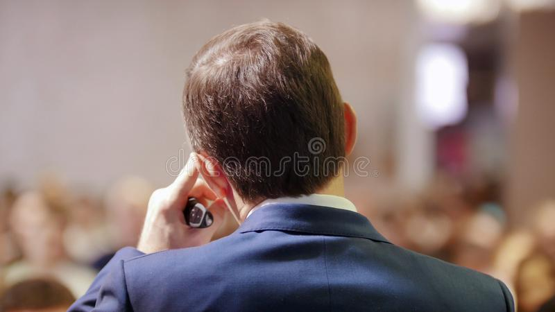 A business conference in the hall. A man talking on the stage to the audience stock photo