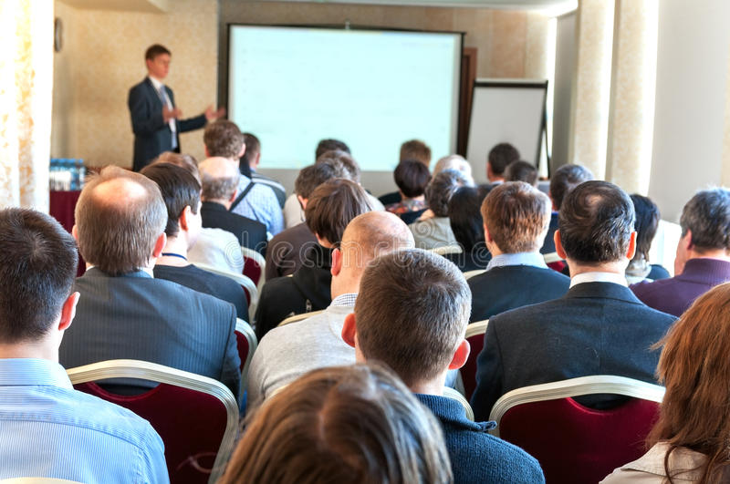 Business conference. People sitting rear at the business conference and the speaker at the screen royalty free stock photography