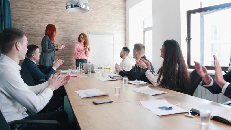 A business conference. A woman explains the charts on the board and people clapping hands royalty free stock photo